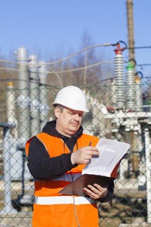 topografo: Ingeniero el�ctrico con la documentaci�n cerca de las subestaciones el�ctricas Foto de archivo