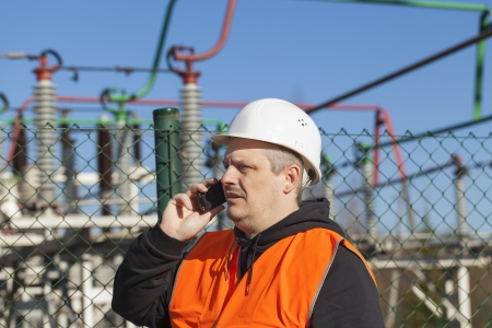 Electrical engineer talking on the phone at the electric substation photo