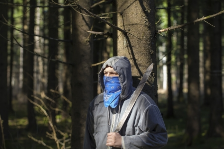 Man with a machete in the woods leaning against tree Stock Photo - 19504755