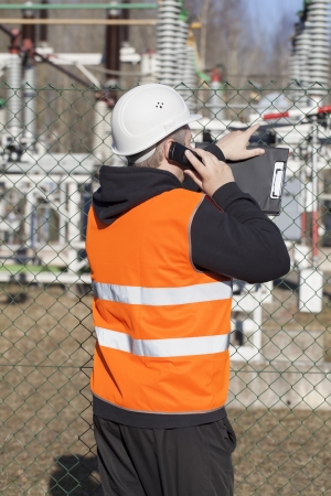 electrical engineer: Electrical engineer talking on the cell phone near to the electric substations