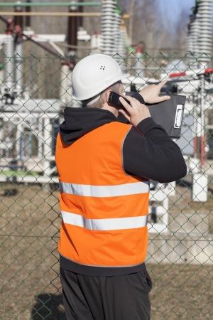 ingenieur electricien: Ing�nieur �lectricien en parlant au t�l�phone cellulaire � proximit� des stations �lectriques