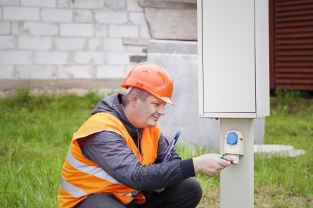 Electrician with folder near switchboard photo