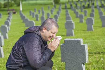military invasion: Man crying on the soldier s grave