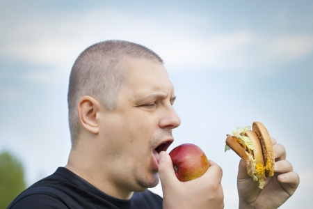 Man with burger and apple in the hands photo