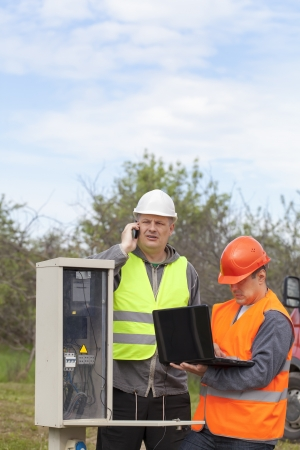 Electricians with PC and folder near switchboard