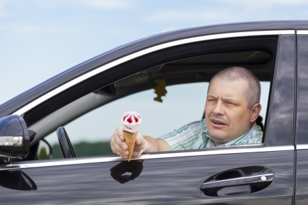 Man sitting in a car offers ice cream photo