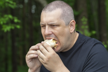 Man eats tortillas with chicken photo