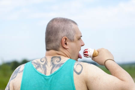 Man with a tattoo on the back with the ice cream in the hands of