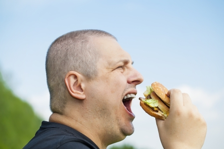Man starting eat burger on a blue sky background photo