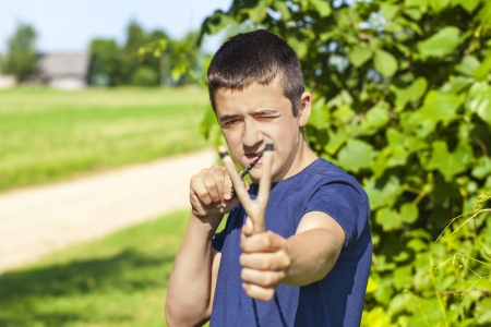 Boy with a slingshot at outdoors in summer