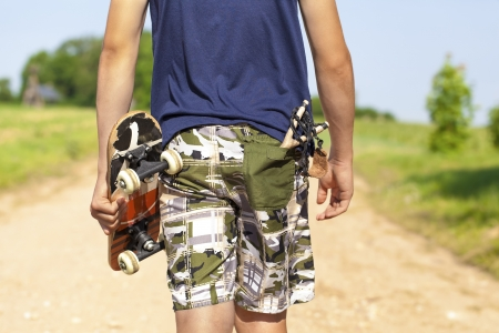 Boy with skateboard and slingshot in pocket on rural road in summer photo
