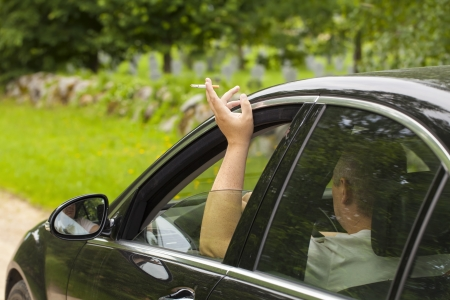 Driver with a cigarette in hands sitting in car Stock Photo - 21122443