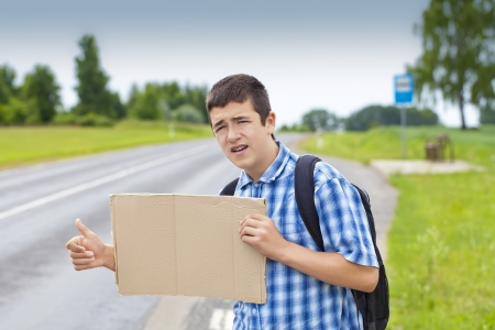 Boy hitchhiker on the road waiting for car to stop photo