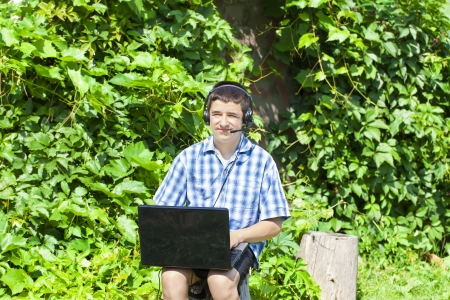 Boy with headphones, Mic and PC at outdoors photo