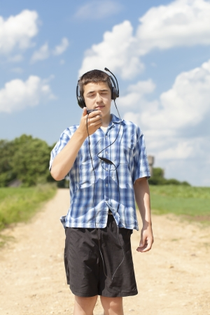 Boy with headphones and Mic on rural road in summer photo
