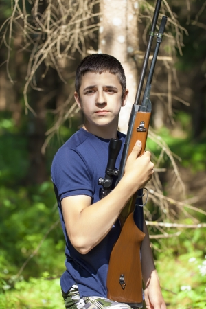 Boy with optical rifle in the woods photo