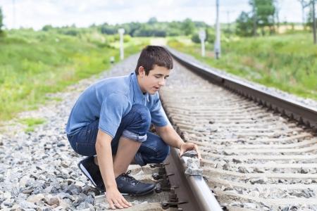 ballast: Boy puts stones on railway tracks