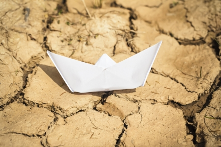 Paper boat on dry land photo