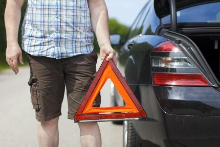 Mann mit Warndreieck in der Nähe von Auto auf der Straße Standard-Bild - 21000152