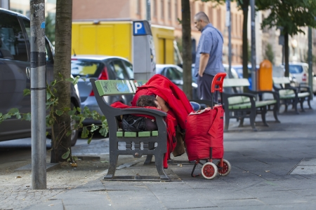 Homeless sleeping on a bench in the street photo
