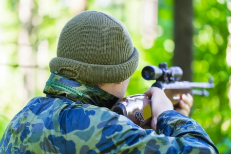 Man with optical rifle   in the woods photo