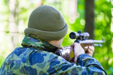 Mann mit Gewehr optischen in den Wäldern Standard-Bild - 21282479