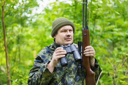 outside shooting: Hunter with optical rifle and binoculars in the woods Stock Photo