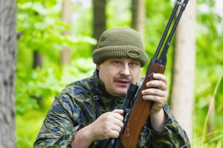 Hunter with optical rifle in forest