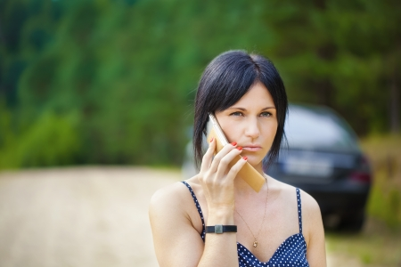 Woman with a cell telephone on the road photo