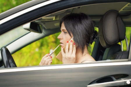 Woman with the lipstick and cell phone in the car photo