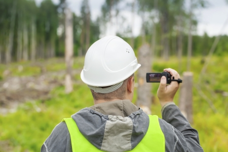 Forest Officer with a video camera filmed deforest photo