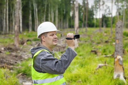 Forest Officer with camcorder filmed deforest Stock Photo