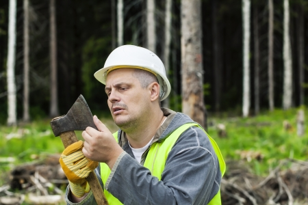 Lumberjack checking ax sharpness in forest photo