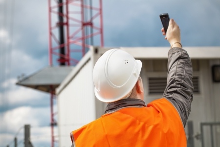 Engineer with the cell phone near to gsm tower Stock Photo