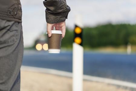 Mann mit Kaffee auf der Autobahn Standard-Bild - 21935682