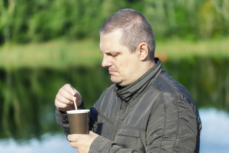 wheater: Man with coffee near river