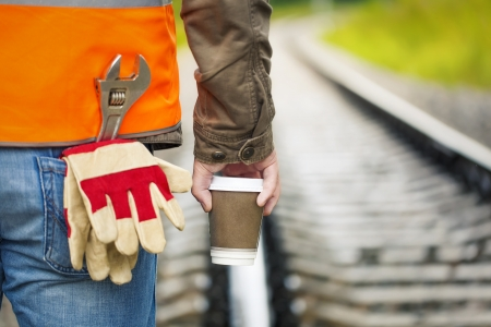 rushed: Worker with a coffee on the rail