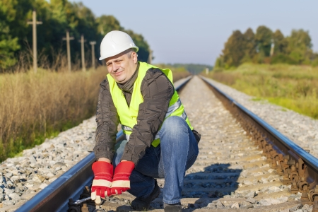 Railroad worker with adjustable wrench on railway photo