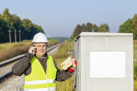 Railroad employee with cell phone near the electrical enclosure