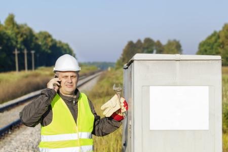 Railroad Mitarbeiter mit Handy in der Nähe des Schaltschranks Standard-Bild - 22223839