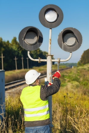 Railway worker dismantles old signal beacons photo