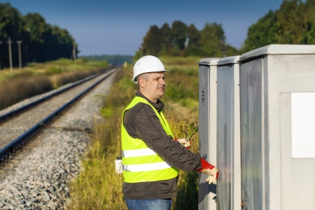 Railroad employee with near the electrical enclosure photo