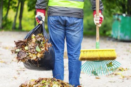 Mann mit Pinsel und Harke sammelt Blätter Standard-Bild - 22477982