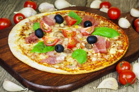 Delicious italian fresh pizza on wooden planks photo