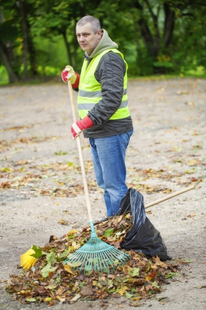 Man with rake collects leaves photo