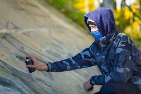 Teenager with color spray can near the wall photo