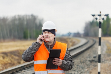 Railroad employee with phone  tablet PC photo