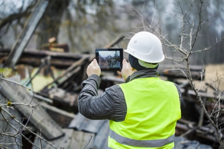 safety helmet: Inspector with tablet PC near collapsed building Stock Photo