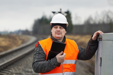 Railroad employee with tablet PC near railway photo