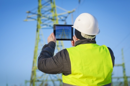 Electrical Engineer with tablet PC near High voltage tower Stockfoto